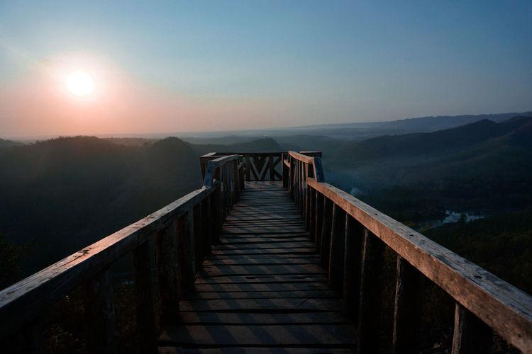 Footbridge against landscape and sky during sunset