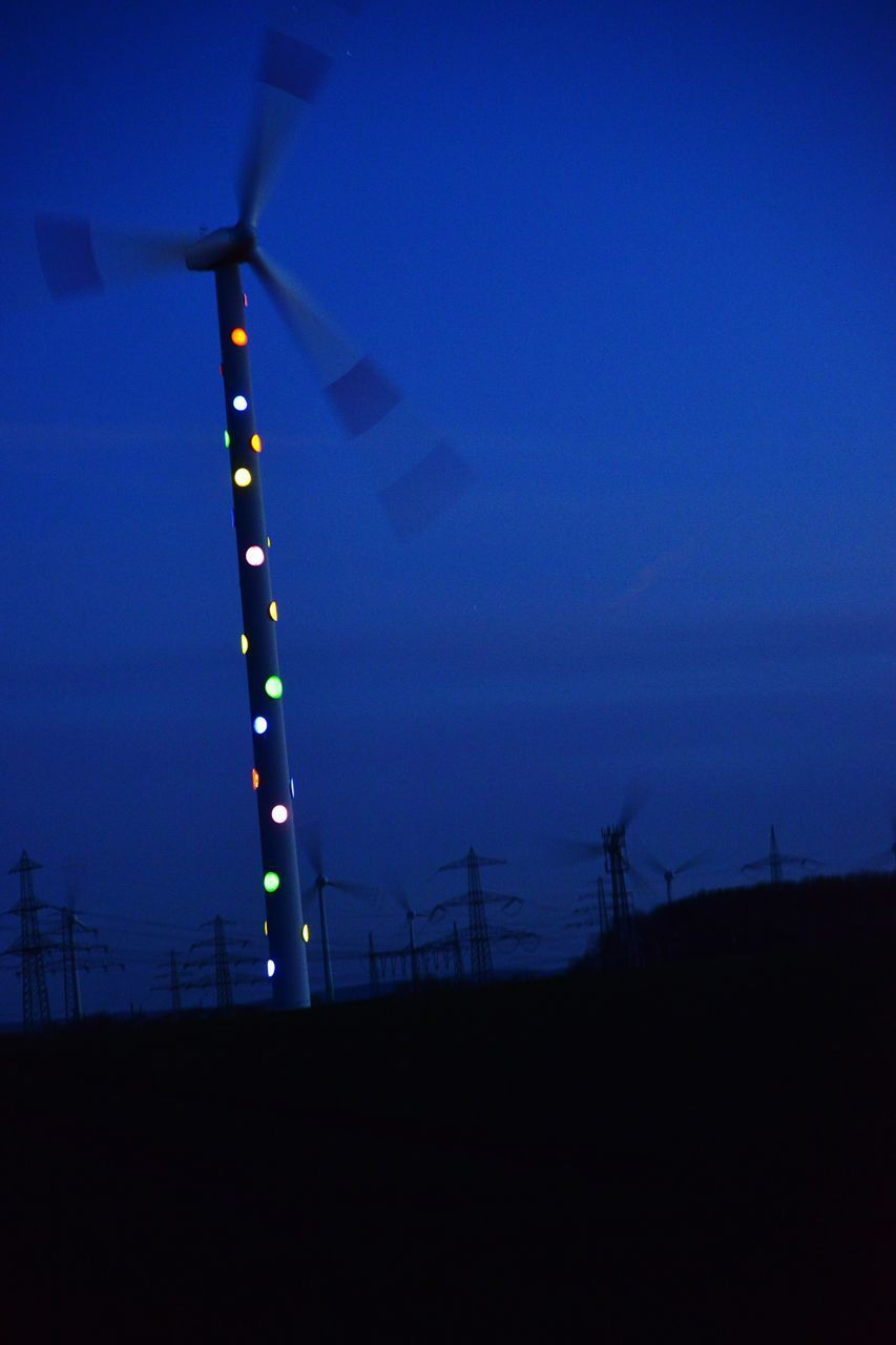 LOW ANGLE VIEW OF WINDMILLS ON FIELD AGAINST SKY AT NIGHT