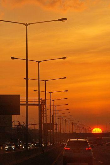 Cars on road in city against orange sky