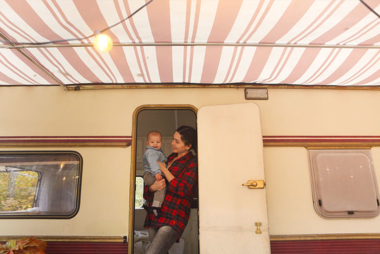 Mother with son standing in motor home
