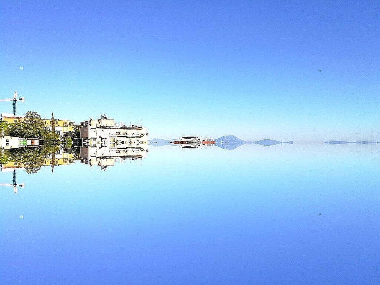water, copy space, blue, reflection, clear sky, architecture, built structure, no people, building exterior, outdoors, day, waterfront, nature, sky, beauty in nature