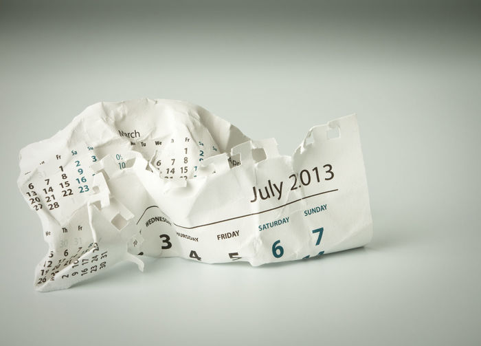 High angle view of crumpled calendar on white background