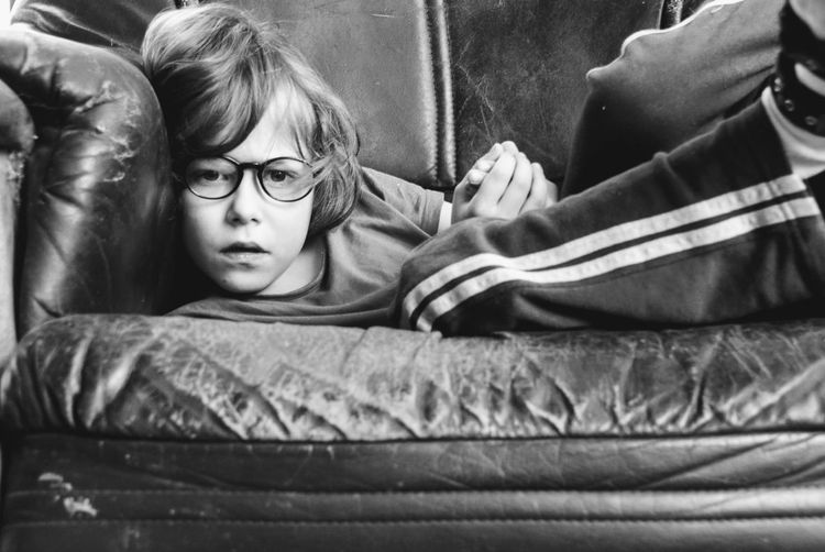 Indoors  People Relaxation Lifestyles Eyeglasses  One Person Real People Close-up Day Boy Loneliness Thoughtful Tired Saddness Thinking Apathetic Indifferent Unconcerned Listless Sad Sitting Incurious Black And White Inquisitive