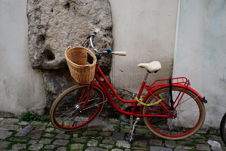 Red Bicycle On Footpath Against Wall