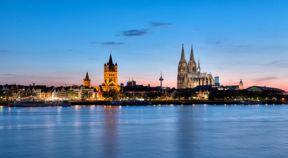 Illuminated buildings and cologne cathedral by rhine river in city at dusk