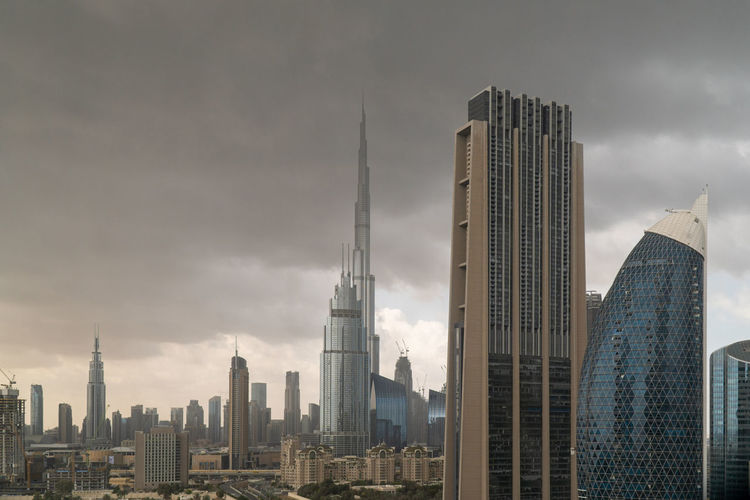 Buildings in city against stormy sky