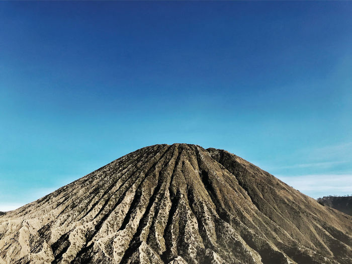 Low angle view of volcanic mountain against clear blue sky,bromo mountain in indonesia.