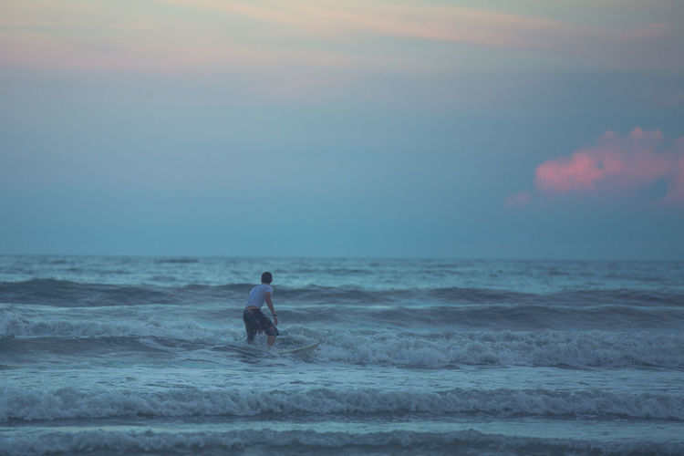 Rear View Of Man Surfing At Sea Against Sky During Sunset