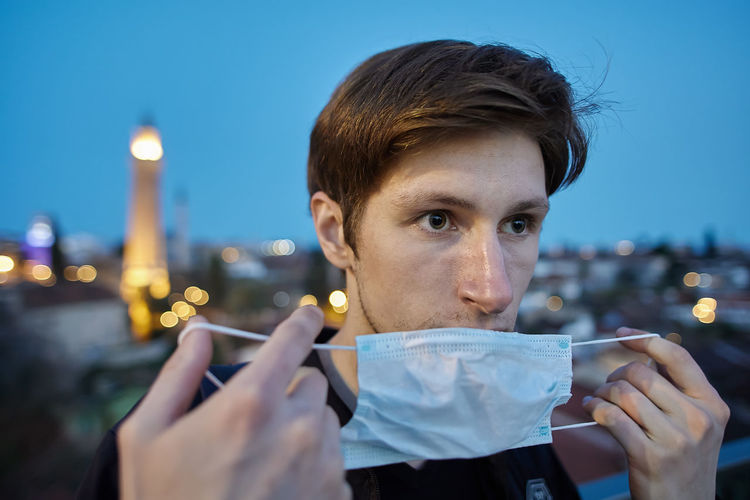 Portrait of young man holding illuminated cityscape against sky