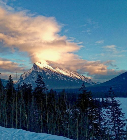 Sun setting on peak of Mount Rundle Day's End Quiet Moments Beauty In Nature Cloud - Sky Cold Temperature Day Illuminated Landscape Mount Rundle Mountain Mountain Range Nature No People Outdoors Peaceful Scenics Sky Snow Snowcapped Mountain Tranquil Scene Tree Winter Been There.