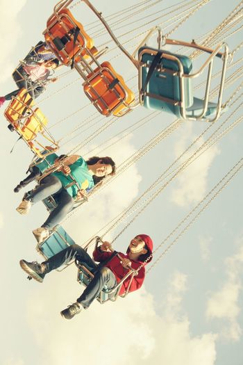 People on chain swing ride against sky