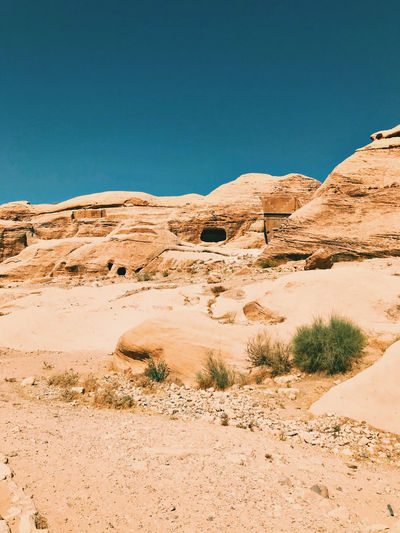 Scenic view of desert rocks against clear blue sky. petra