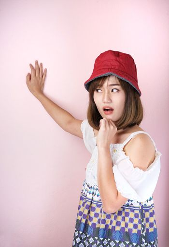 Shocked young woman standing against pink background