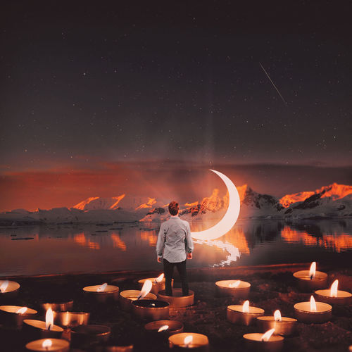 Digital composite image of man standing in tea light candle against lake and moon at night