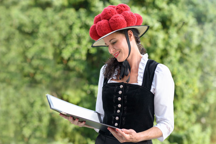 Waitress wearing hat while reading menu against trees