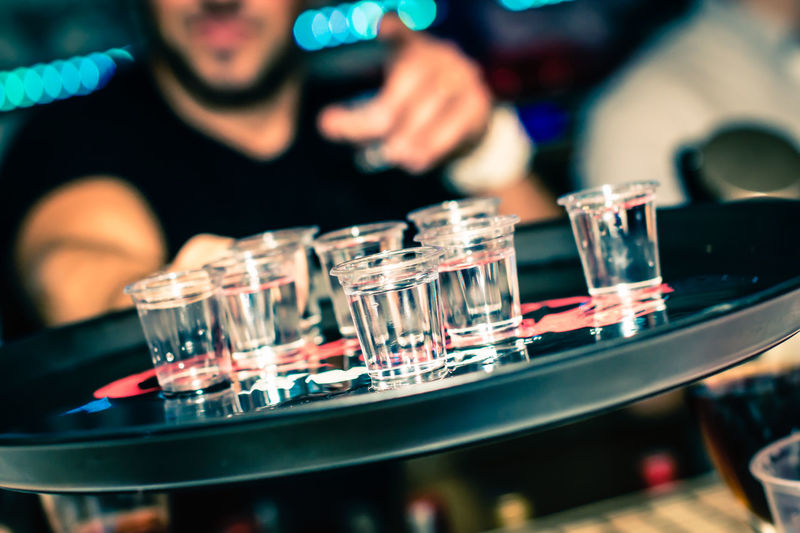 Tilt Shot Of Bartender Offering Drinks On Tray At Bar