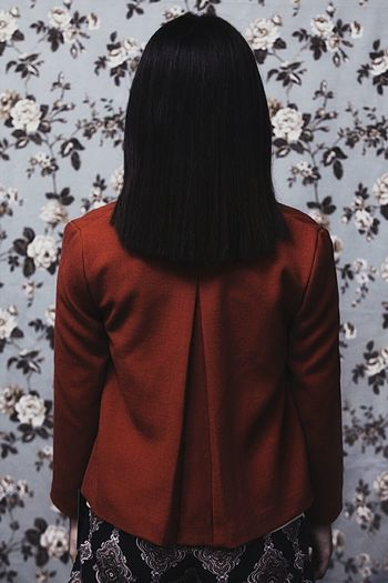 Rear view of woman with straight hair against wall at home