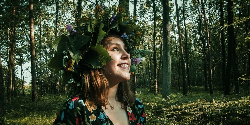 Smiling young woman wearing tiara standing in forest