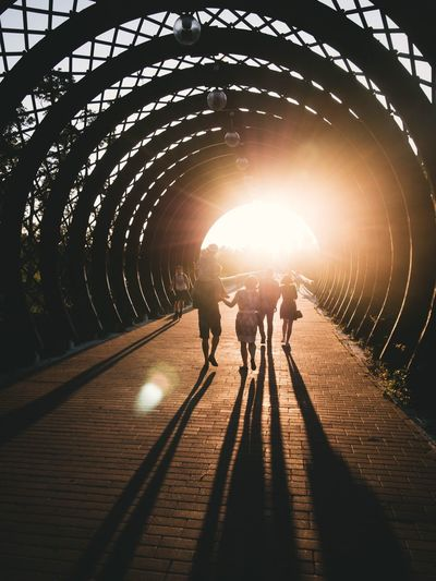 People Walking In Covered Bridge During Sunset