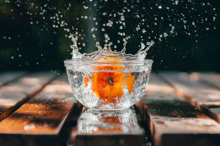 Close-up of glass of water splashing on table