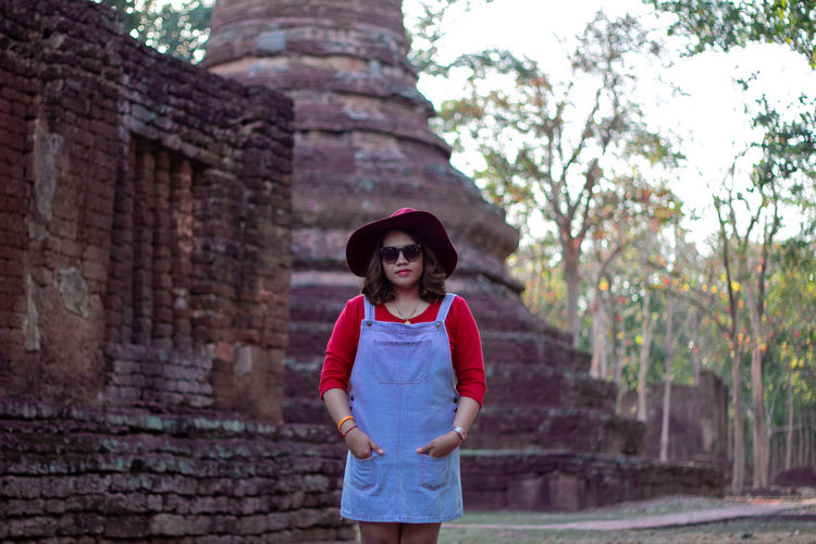 Young woman wearing hat and sunglasses against historic temple