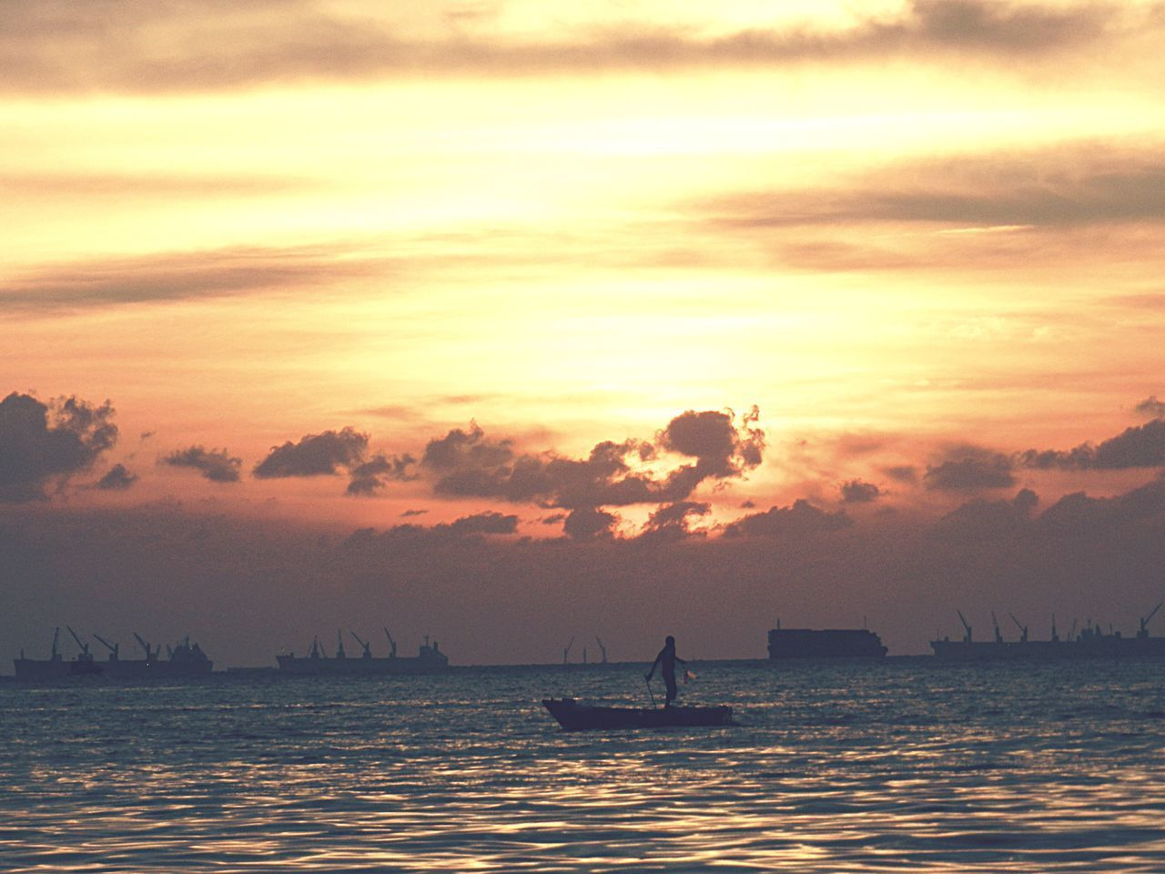 sunset, nautical vessel, transportation, water, mode of transport, beauty in nature, scenics, silhouette, nature, boat, sky, orange color, sea, tranquil scene, tranquility, cloud - sky, outdoors, real people, waterfront, sailing, men, longtail boat, horizon over water, rowing, oar, one person, jet boat, day, people
