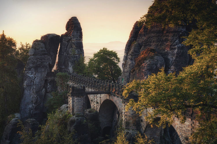 Arch Bridge And Rock Formations Against Sky During Sunset