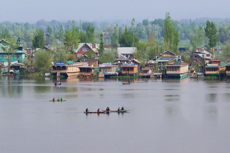 People on lake by houses against trees and plants