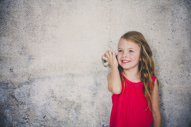 Cute smiling girl playing with tin can phone while standing against wall