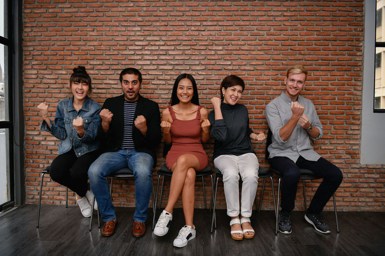 Portrait of happy colleagues gesturing while sitting on chairs against brick wall in office