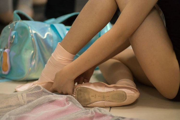 Low section of woman wearing ballet shoes while sitting on floor