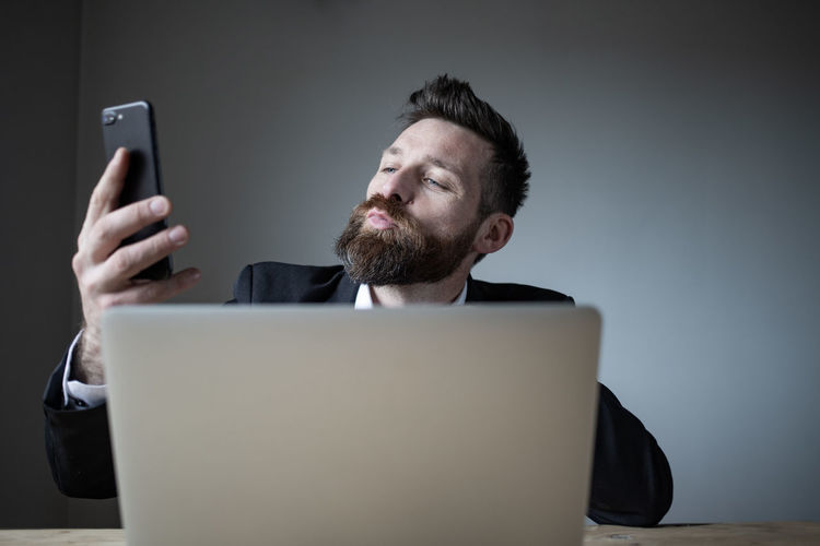 Midsection of man holding smart phone