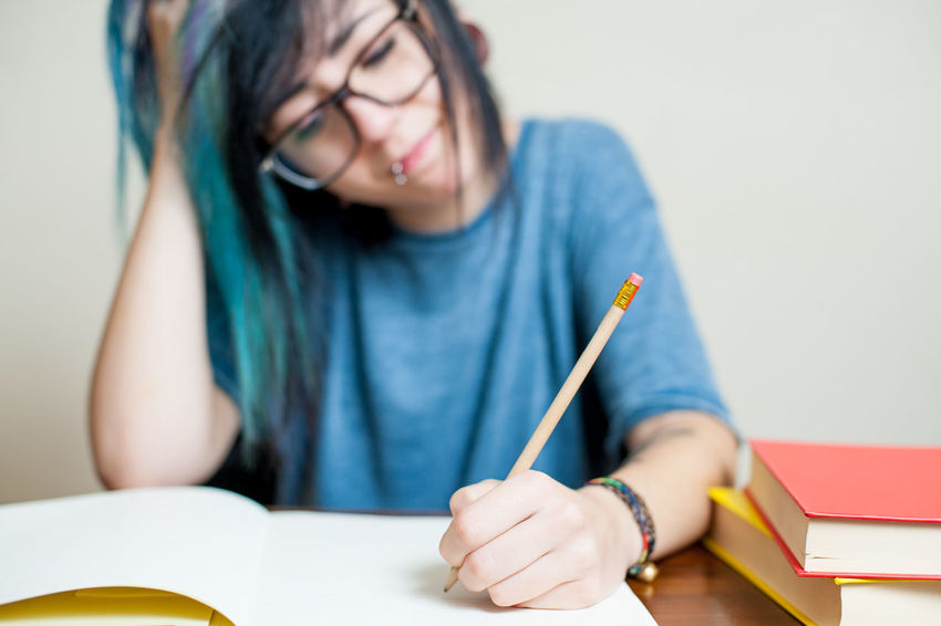 Pretty teen hypster style woman student tired writing on books Alternative Blue Book Cute Day Desktop Difficult Examination Eyeglasses  Girl Hypster One Person Pretty School Student Studying Teen Teenager Test Tired Woman Young