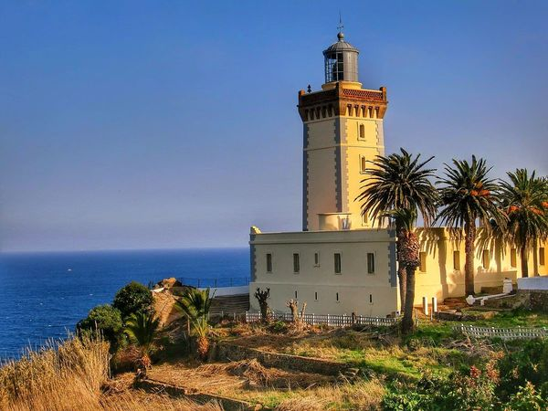Architecture Lighthouse Tower Building Exterior Beach Sea Travel Destinations Sky Clock Tower Outdoors History Blue Clear Sky Day Tree No People Horizon Over Water Vacations Water Sand Dune Tangier Morocco
