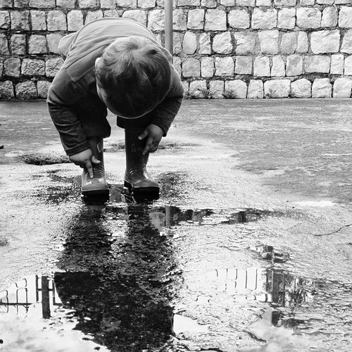 Boy Touching Boot With Reflection On Puddle