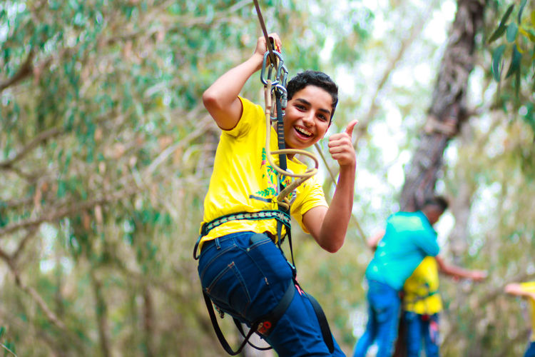 Portrait of smiling teenage boy zip lining with man in background at forest