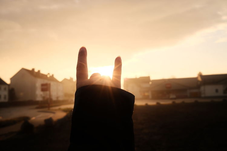 Hand against sky during sunset