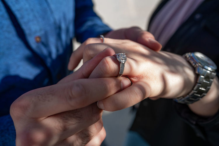 Close-up of man wearing engagement ring to woman