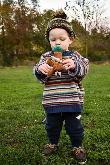 Cute boy holding toy while standing on field