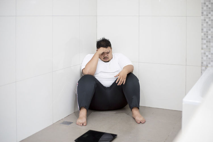 Overweight man sitting with weight scale in bathroom