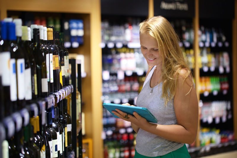Woman using digital tablet while standing at wine store