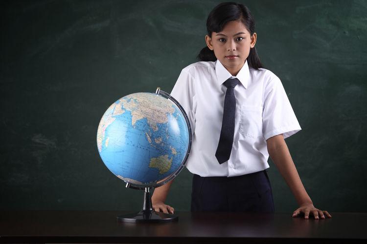 Schoolgirl with globe against blackboard