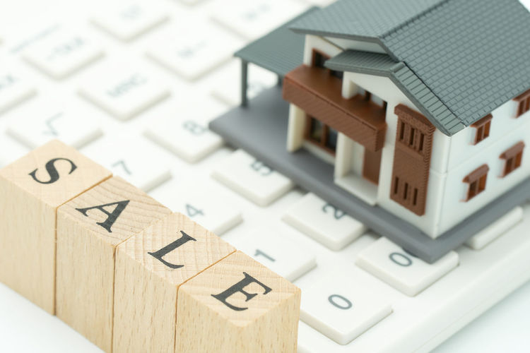Close-Up Of Model House On Keyboard With Text Over Table