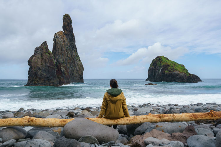 Janela Islets in Porto Moniz in Madeira with a woman sitted on a yellow tree on the ground Madeira Portugal Island Ilha Travel Landscape Nature Mountain Yellow Tree Outdoors Beach Porto Moniz Ribeira Da Janela Islet Panorama Panoramic Seascape Sea Europe Waves Girl Woman Alone Traveler