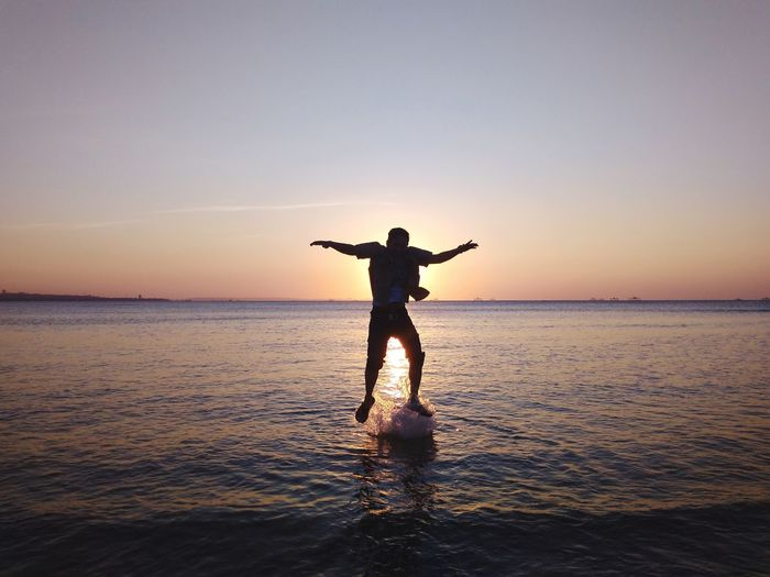 Full length of man jumping in sea against sky during sunset
