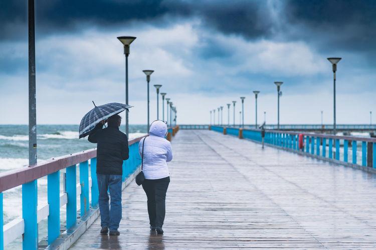 Rear view of people walking on street during rain
