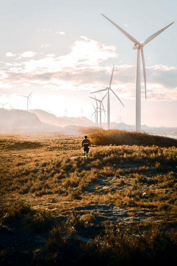 Man walking by wind mill against sky