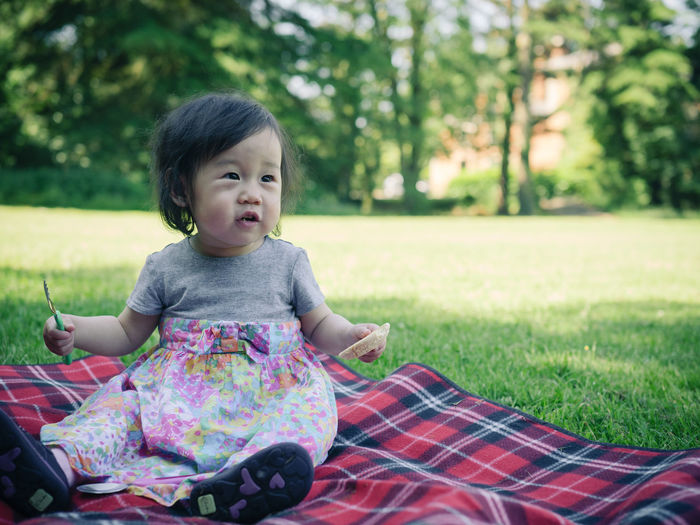 Cute girl eating food while sitting on picnic blanket over grassy field at park