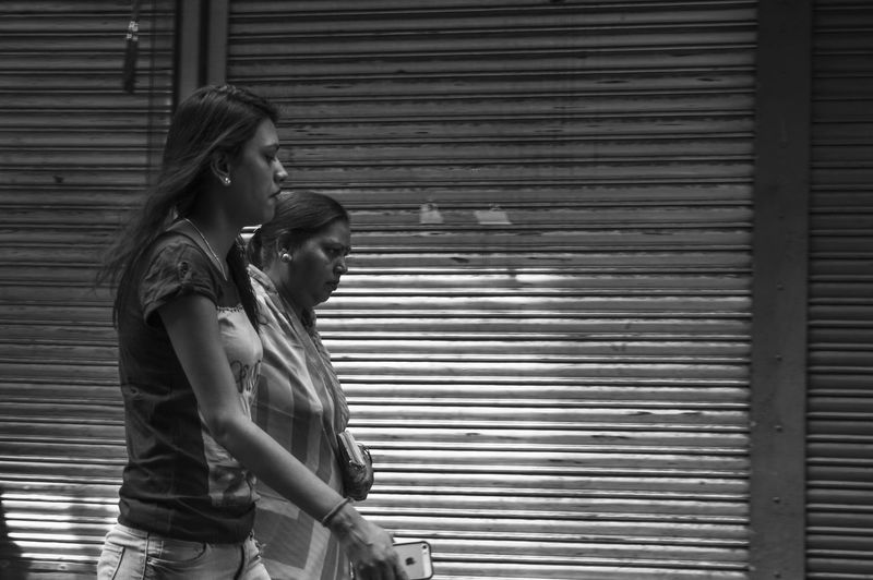 Side view of woman standing against shutter