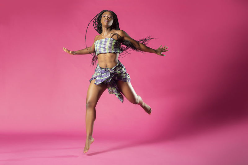 Beautiful African Black girl wearing traditional colorful African outfit does a dramatic dance move against a colorful pink background African African Traditions Adult African Dancer African Woman  Beautiful Woman Beauty Clothing Colored Background Dandelion Fashion Full Length Hairstyle Indoors  Lingerie Long Hair Motion One Person Pink Background Pink Color Portrait Studio Shot Tradition Dress Women Young Adult Young Women